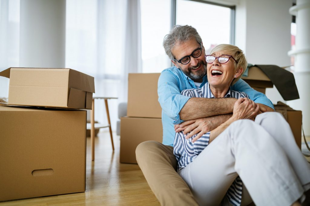 Happy retired senior couple moving into a new home, apartment